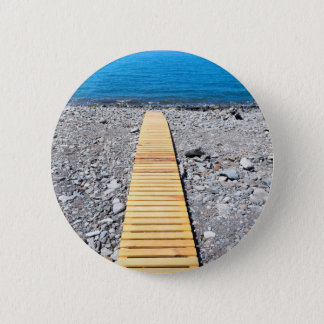 Wooden footpath on beach leading to portuguese sea 2 inch round button