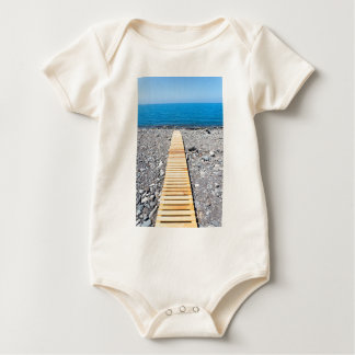 Wooden footpath on beach leading to portuguese sea baby bodysuit