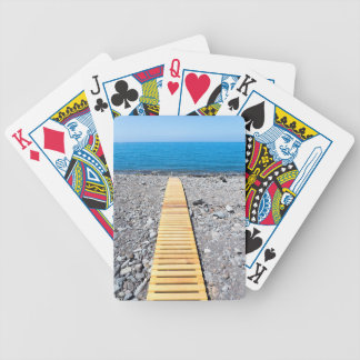 Wooden footpath on beach leading to portuguese sea bicycle playing cards