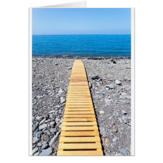 Wooden footpath on beach leading to portuguese sea card