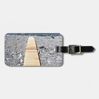 Wooden footpath on beach leading to portuguese sea luggage tag