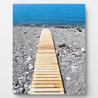 Wooden footpath on beach leading to portuguese sea plaque