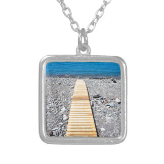Wooden footpath on beach leading to portuguese sea silver plated necklace