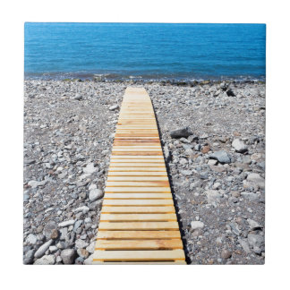 Wooden footpath on beach leading to portuguese sea tile