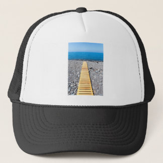 Wooden footpath on beach leading to portuguese sea trucker hat