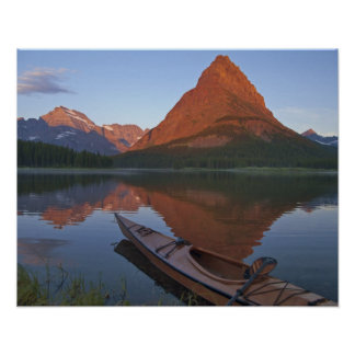 Wooden kayak in Swiftcurrent Lake at sunrise in Poster
