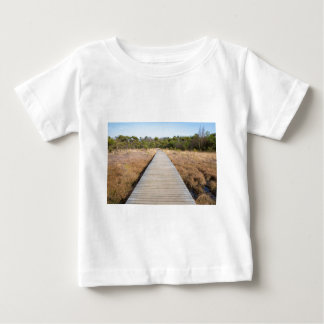 Wooden path in grass and forest winters landscape. baby T-Shirt