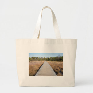 Wooden path in grass and forest winters landscape. large tote bag