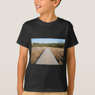 Wooden path in grass and forest winters landscape. T-Shirt