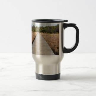 Wooden path in grass and forest winters landscape. travel mug