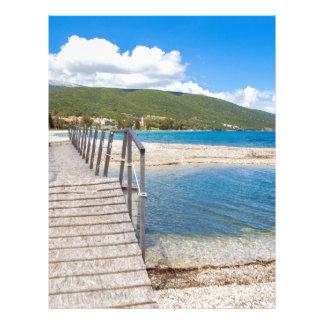 Wooden pedestrian bridge on greek beach letterhead