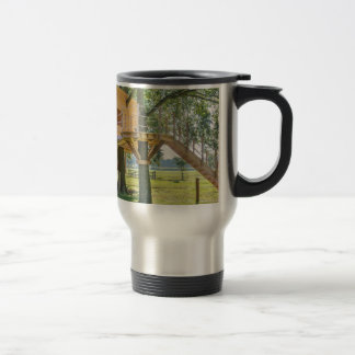 Wooden tree house in oak tree with grass travel mug