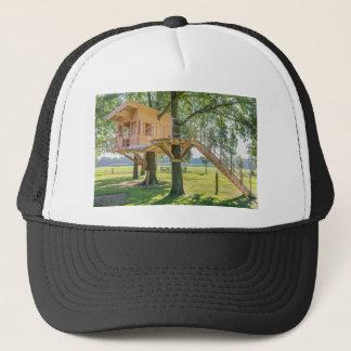 Wooden tree house in oak tree with grass trucker hat