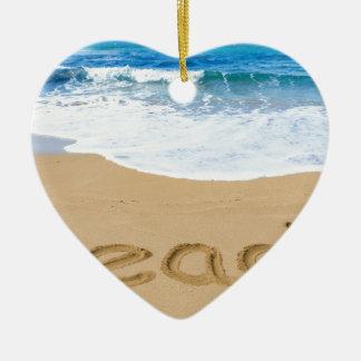 Word beach on sandy coast with blue sea ceramic heart ornament