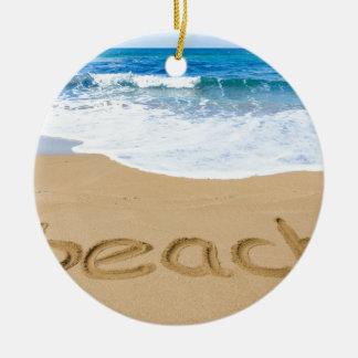 Word beach on sandy coast with blue sea round ceramic ornament