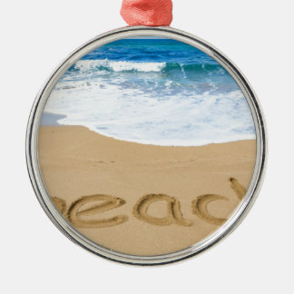Word beach on sandy coast with blue sea Silver-Colored round ornament