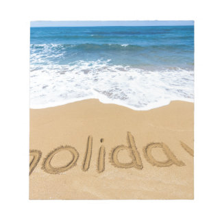 Word holiday written in sand on beach notepad