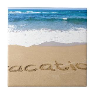 word vacation written on sand beach at sea tile