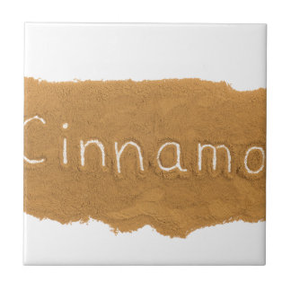 Word written in Cinnamon powder on white backgroun Tile