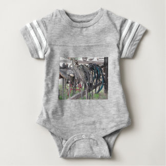 Worn leather horse bridles hanging on wooden fence baby bodysuit