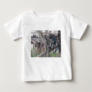 Worn leather horse bridles hanging on wooden fence baby T-Shirt