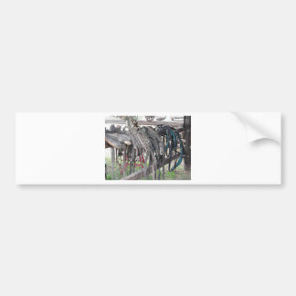 Worn leather horse bridles hanging on wooden fence bumper sticker