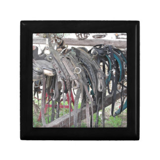 Worn leather horse bridles hanging on wooden fence gift box