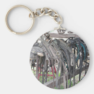 Worn leather horse bridles hanging on wooden fence keychain