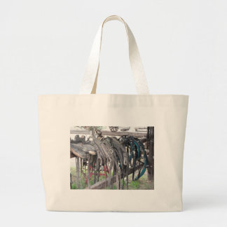 Worn leather horse bridles hanging on wooden fence large tote bag