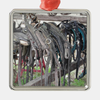 Worn leather horse bridles hanging on wooden fence metal ornament