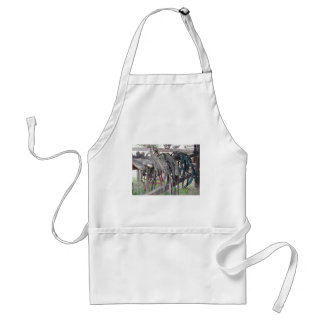 Worn leather horse bridles hanging on wooden fence standard apron