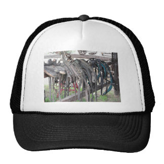 Worn leather horse bridles hanging on wooden fence trucker hat