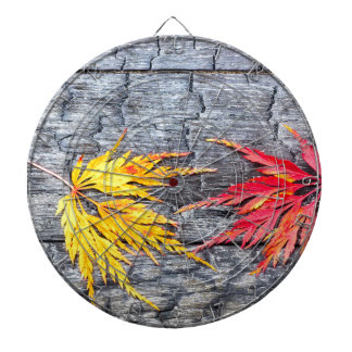 Yellow and red maple leaf on black burnt wood dart board