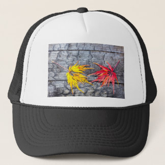 Yellow and red maple leaf on black burnt wood trucker hat