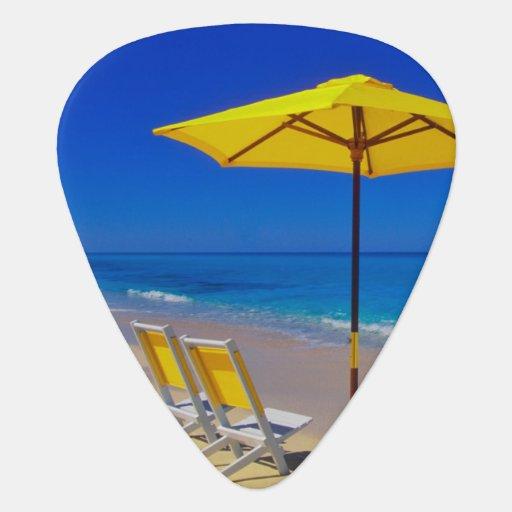 Yellow beach umbrella and chairs on pristine guitar pick