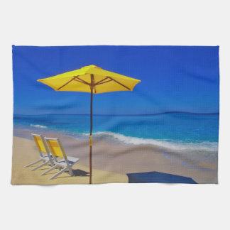Yellow beach umbrella and chairs on pristine towel