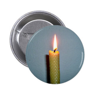 Yellow Candle flame against white wall Button