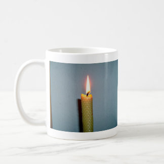 Yellow Candle flame against white wall Mug