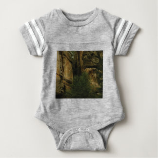 yellow rock face with trees baby bodysuit