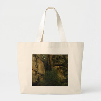 yellow rock face with trees large tote bag