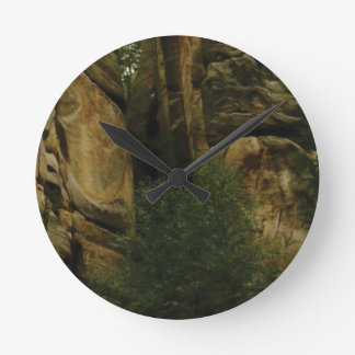 yellow rock face with trees round clock