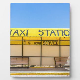 Yellow taxi station at coast in Greece Plaque