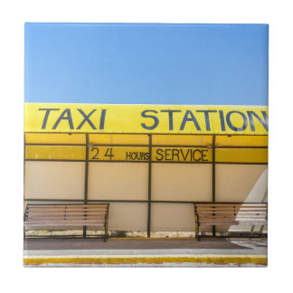 Yellow taxi station at coast in Greece Tile