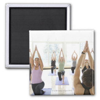 Yoga instructor leading class through the square magnet