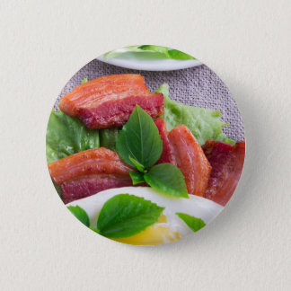 Yolk, fried bacon, herbs and lettuce close-up 2 inch round button