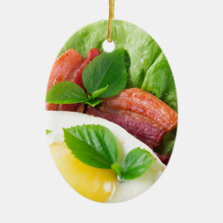 Yolk, fried bacon, herbs and lettuce close-up ceramic oval ornament