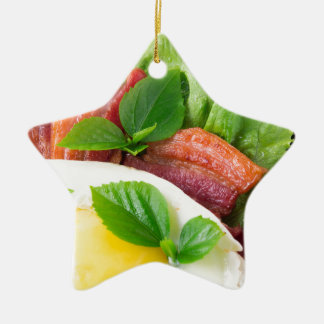 Yolk, fried bacon, herbs and lettuce close-up ceramic star ornament