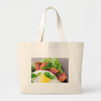 Yolk, fried bacon, herbs and lettuce close-up large tote bag