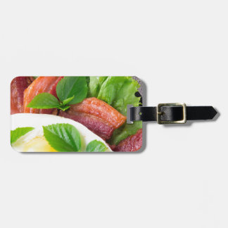 Yolk, fried bacon, herbs and lettuce close-up luggage tag