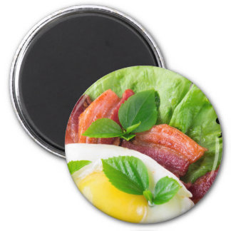 Yolk, fried bacon, herbs and lettuce close-up magnet